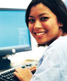 smiling young woman at keyboard.